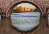 A shot under a bridge in the river with a castle on the horizon