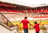 A man and boy, father and son, Man U fans, in the player's tunnel looking out on to the pitch during a stadium tour.