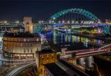 Night time view of the Tyne Bridge, Swing Bridge and Sandhill, Newcastle-upon-Tyne, England lit up at night.