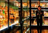 Woman standing inside The Scotch Whisky Experience in Edinburgh, Scotland. 3,384 whisky bottles stored in one large display.