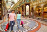 A couple walk through a shopping centre carrying shopping bags