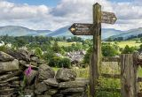 Footpath in Hawkshead, Lake District, Cumbria, England. Drystone wall, wooden gate and signpost.