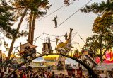 Crowds walking under a bridge of fantasy vehicles and tightrope walker at Bestival, Lulworth Estate, Dorset, England
