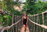 Girl walking across a suspension bridge with green trees in the background
