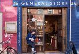 Bearded man sitting outside Deadstock General Store, 46 Edge St, Manchester, England, UK.