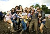 A group of young people holding drinks in a muddy field enjoying V Festival