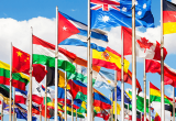 Image of country flags on flagpoles  including Australia and Canada flying in the breeze against a blue sky