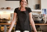 Young woman in a black apron standing behind the counter of a cafe with pastries and coffee cups on the counter