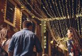 A man and two women walk under a row of fairy lights