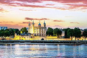 Twilight view of the Tower of London from across the Thames River with a pink sky