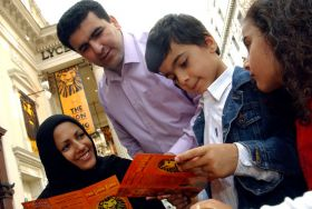 An Arab family reading a Lion King leaflet