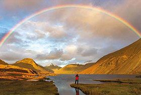Wast Water, Lake District, Cumbria, England. Person standing at the edge of the lake, watching a rainbow in cloudy sky.