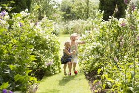 Children running through a sunny garden