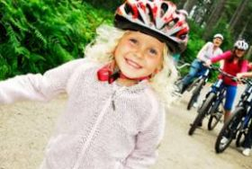 A smiling little blonde girl on a bike wearing a pink bike helmet with family on bikes in the background