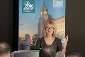 Lady speaking infront of an IFB banner