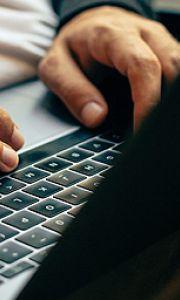 Man typing on laptop on his lap