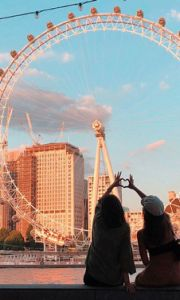two girls in front of London Eye making a heart with their hands