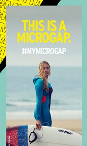 Woman stand on a beach wearing a wetsuit, holding a surfboard. The text reads 'This is a microgap, #microgap'