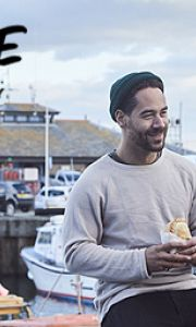 Man eating Cornish pasty, Padstow Harbour, Padstow, Cornwall, England.