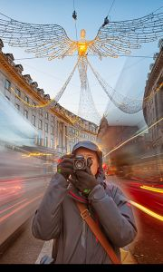 figure stood on a busy city street facing out of the image with a camera held up to their eye, and light trails of moving traffic in the background