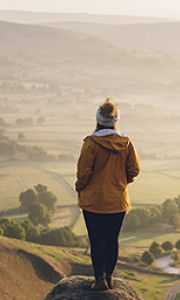 A woman standing looking at the view from Winnats Pass, Peak District of Derbyshire