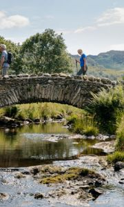 A tour group of senior people crossing a bridge in the countryside