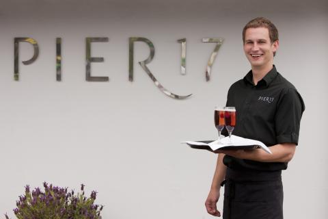 Waiter serving champagne cocktail at Pier 17 restaurant, St Peter port, Guernsey, UK