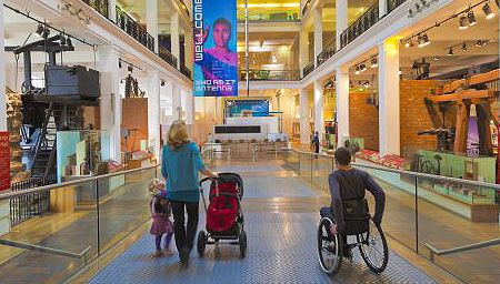 A man in a wheelchair visiting a museum, alongside a woman with a child and pushing a pram
