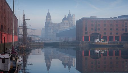 Historic ship moored at Maritime Albert Dock on Liverpool waterfront with the Three Graces historic buildings, in the distance, Liverpool, Merseyside, England.