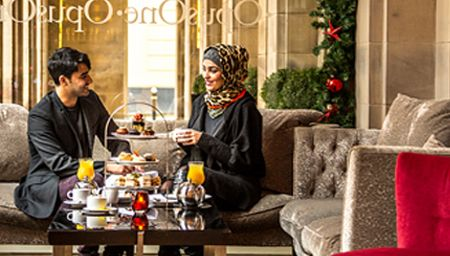 Arabian couple having afternoon tea in luxury hotel in Manchester