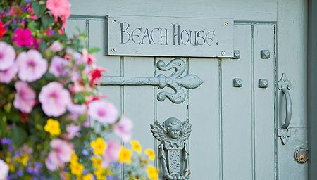 A small painted wooden door with a sign and flowers in front. Guest house accommodation in the North York Moors National Park.