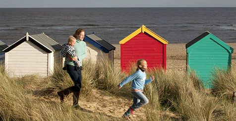 A woman holding a baby and a young child run across a sand bank behind beach huts