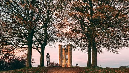 View of the Broadway Tower through trees in The Cotswolds, Worcestershire, England.
