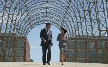 A man and woman in businesswear talking and walking under a walkway