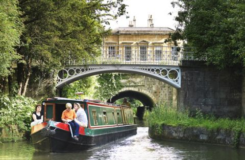 People on a canal boat near a picturesque bridge