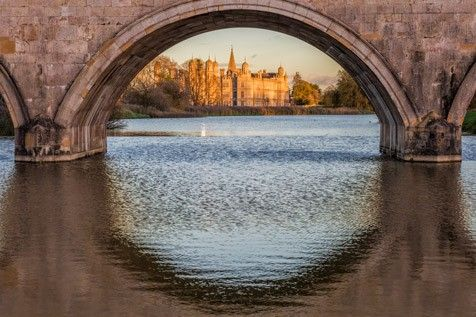 A bridge arch reflected in water
