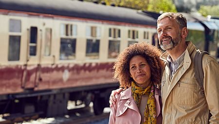Smiling couple hugging on Bath Station platform, with a red and cream train in the background.