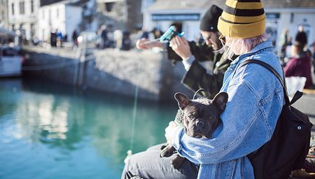 A woman in a yellow beanie and blue jacket holding her French bulldog and sitting on a harbour wall at Padstow Harbour, Padstow, Cornwall, England