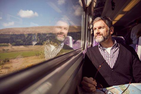 Man by window in train