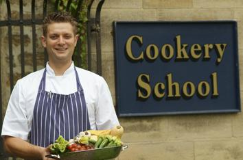 A young male chef standing outside of a cookery school holding a bowl of vegetables