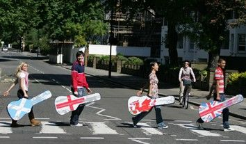 Four people recreating The Beatle's Abbey Road album cover with guitar cases with flags for Scotland, England, Wales and UK
