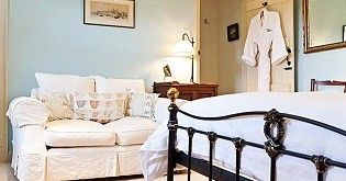 A guest bedroom in a hotel. It includes a white double bed with a white sofa and a dressing gown hung on the back of the door