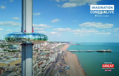 British Airways i360 in foreground with a view over Brighton Beach on a clear sunny day. Imagination comes alive tagline on image