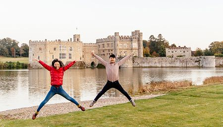 Couple jumping on a lawn by the moat at Leeds Castle near Maidstone, Kent, UK.