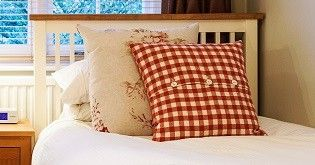 A single bed in a bedroom with a red and white checked pillow