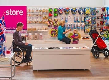 A man in a wheelchair and woman with a pushchair in a museum shop