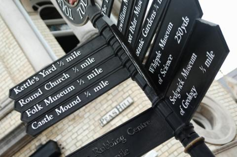 A black signpost in Cambridge featuring directions and distances to Kettle's Yard, Castle Mound, Folk Museum and Round Church