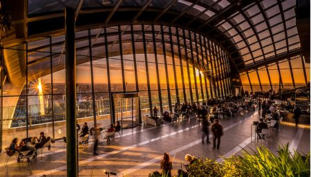 Interior view of the Sky Garden, London, England. People sitting at tables with the sun setting over the London skyline seen through the large glass window.