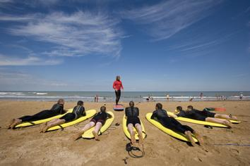 A group of surfers in black wet suits laying on their yellow surf boards on the beach listening to their surf instructor