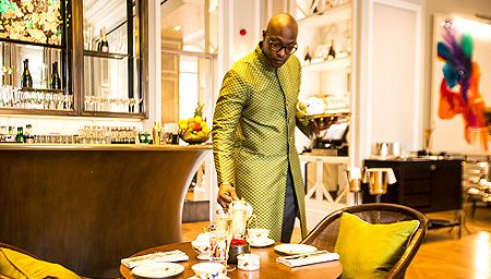 A man in an elegant long green jacket lays the table for an afternoon tea at the Mandarin Orient Hotel.